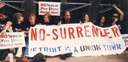 Members of RADD (Radical Action Disciple Deployment Team) handcuff themselves to the front doors of the Detroit Free Press in support of the Detroit Newspaper Strike. (Photo via the Reuther Library)